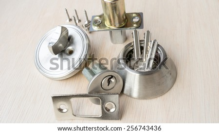 Collection of small parts to create a complete metal deadbolt lock on clean wooden surface - stock photo