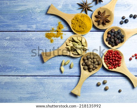 Collection of spices on wooden spoons and a blue wooden table. - stock photo