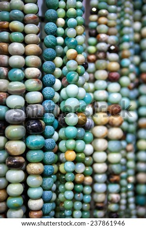 Collection of stone beads jewelry in a market. - stock photo