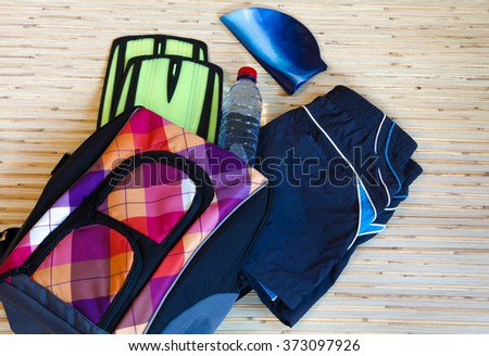 Collection of swimming equipment, flippers, cap, spilling out of the bag on the background for the school swim team background or competitive swim teams. The view from the top. - stock photo