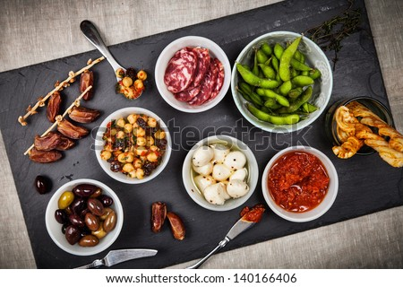 Collection of tapas foods including dates, chickpea salad, salami, fresh mozzarella, edamame, and olives on a slate board. - stock photo