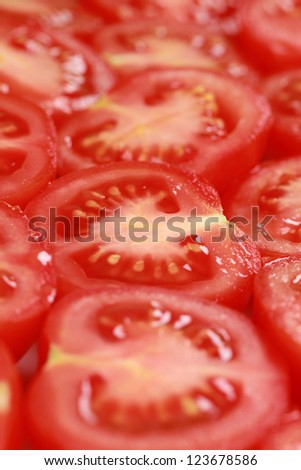 Collection of tomatoes cut in slices and forming a background - stock photo
