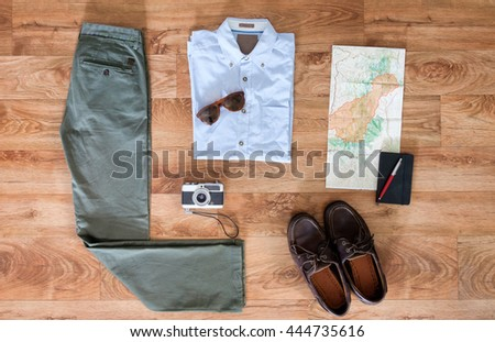 Collection of traveler clothes on wooden background
