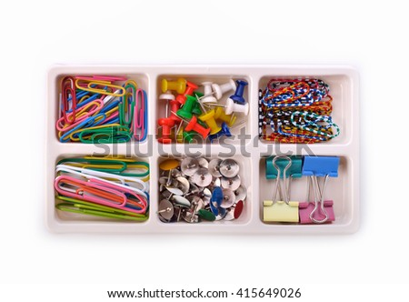 Collection of various pins and paper clips in a plastic tray on white background. - stock photo