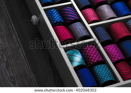 Collection of vibrant coiled ties on display. Close up photo of group of luxury neckties in shop