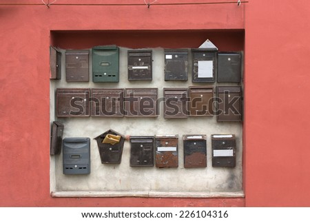 Collection of wall-mounted mail boxes in a recess in a pink wall belonging to an apartment building or flats in different styles and designs - stock photo