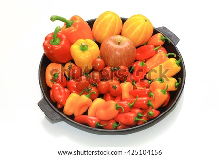 Collection of warm color vegetables, paprika, apple, cherry tomato and oriental melon on the iron plate. Detox and diet food. - stock photo