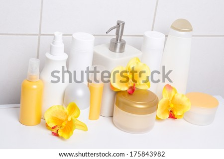 collection of white cosmetic bottles and hygiene supplies with orange orchids over tiled wall in bathroom - stock photo