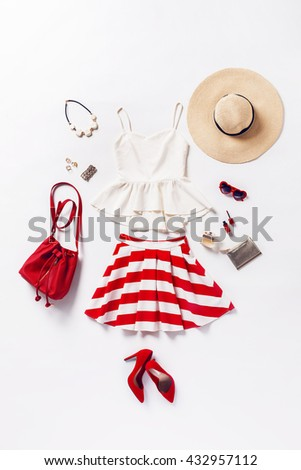 collection of women's clothing and accessories. Overhead of essentials young woman. Outfit of casual and elegant woman, red shoes, summer hat, handbag, high heels shoes, sunglasses. - stock photo