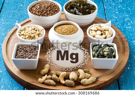 Collection products containing magnesium (buckwheat, cashews, peanuts, pine nuts, almonds, flax seeds and pumpkin, mustard, seaweed) on a round cutting board and a blue wooden background - stock photo