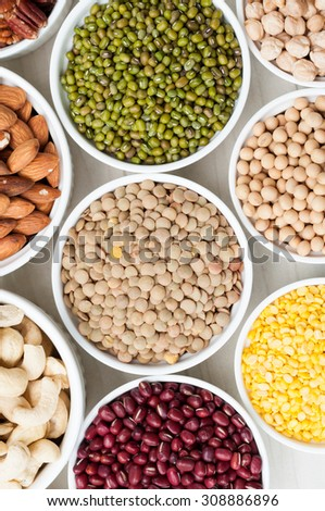 collection set of beans, legumes, peas, lentils on ceramic bowl on white wooden background - stock photo