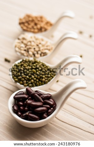 collection set of beans, legumes, peas, lentils on ceramic spoons on white wooden background - stock photo