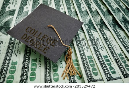 College Degree graduation cap on assorted hundred dollar bills                                - stock photo