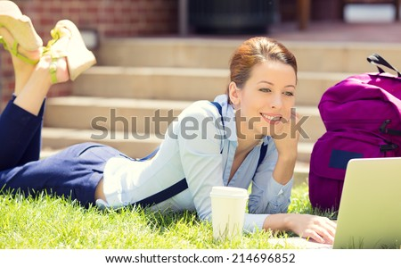 College female student lying down on lawn grass working on laptop at university campus outside on sunny summer day. Education, technology concept. Positive human emotions, facial expressions, feelings - stock photo