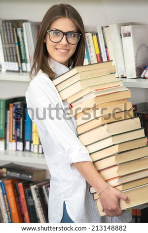 College female student on university campus holding many books in hands - stock photo