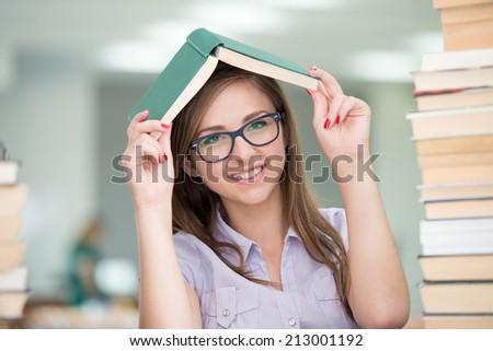 College female student on university campus with pile of books - stock photo