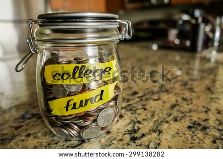 "College Fund Money Jar. A clear glass jar filed with coins and bills, saving money. The words ""College Fund"" written on the outside. - stock photo"