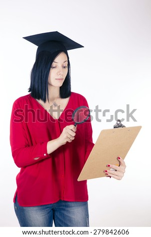 college girl looking through a magnifying glass - stock photo