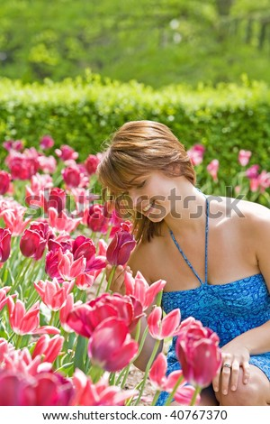 College Girl Smelling the Pretty Pink Tulips - stock photo