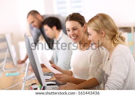 College girls working in front of desktop - stock photo