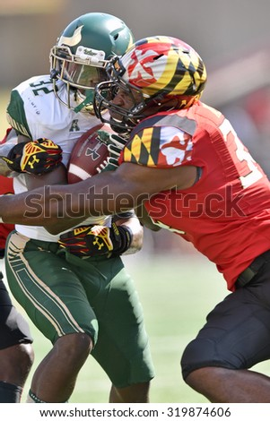 COLLEGE PARK, MD - SEPTEMBER 19: South Florida Bulls running back D'Ernest Johnson (32) is hit hard by a Terp defender during a NCAA football game September 19, 2015 in College Park, MD.  - stock photo