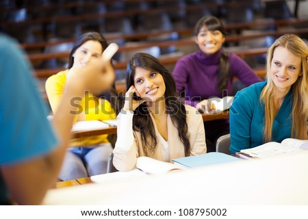 college professor lecturing group of students in classroom - stock photo