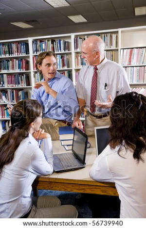 College professor with diverse group of student talking in library - stock photo