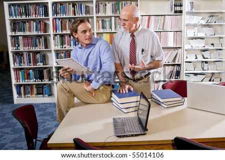 College professor with male student conversing in library - stock photo
