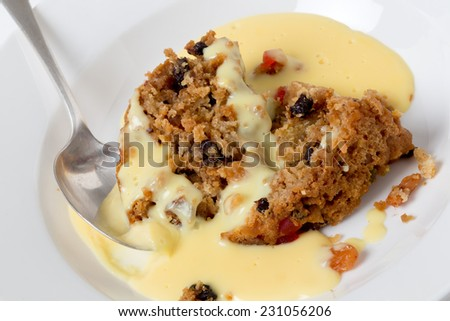 College pudding, the traditional steamed  dessert served to students at Oxford and Cambridge, containing dried fruits, candied peel, flour, sugar, bread, egg and suet served with custard. - stock photo