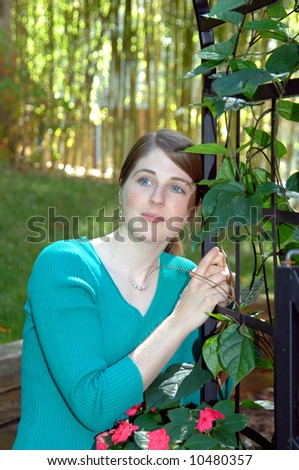 College student leans against an iron gate in a garden.  Flowers and ivy climb ironwork.  Serene expression on females face.