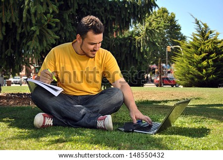 college student lying on the grass in the sun with a computer - stock photo