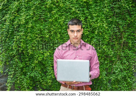 College student studying in peaceful, green environment. Wearing red patterned, long sleeve shirt,  a young guy standing against wall with green leaves on campus, reading, working on laptop computer. - stock photo