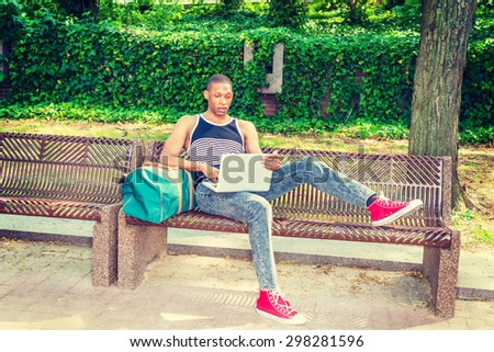 College Student Studying in Summer in New York. Wearing black, white striped tank top, jeans, red sneakers, carrying bag, a black guy sitting on chair on campus, reading, working on laptop computer.  - stock photo