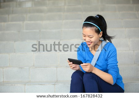 college student use smart phone sit on stairs  - stock photo