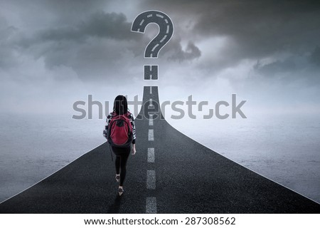 College student walking on the highway while looking at a question mark - stock photo