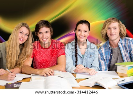College students doing homework in library against glowing abstract design