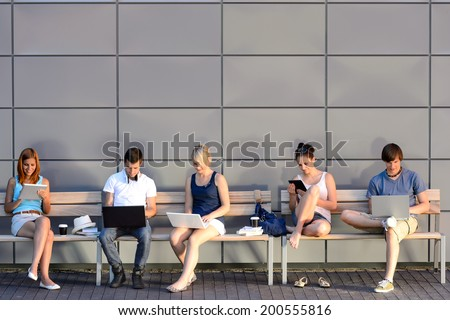 College students internet computer addiction sitting bench outside campus summer - stock photo