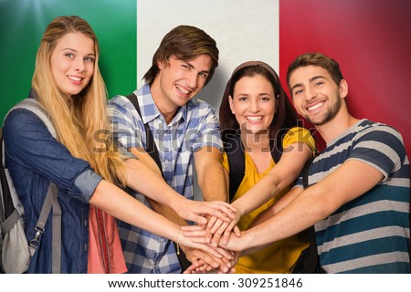 College students placing hands together against italy national flag - stock photo