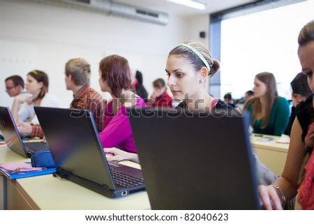 college students sitting in a classroom, using laptop computers during class (shallow DOF)
