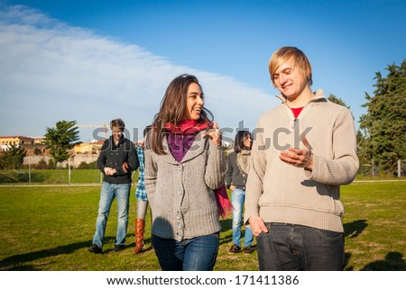 College Students Walking and Talking at Park - stock photo