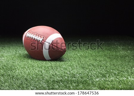 College style football on grass field against dark background