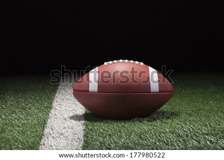 College style football on grass field and stripe at night low angle - stock photo