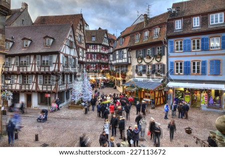 COLMAR,FRANCE-DEC 6:People walking in a square with traditional half-timber houses and Christmas decorations in Colmar, France on December 6, 2013.Colmar is the capital of Alsatian wine. - stock photo