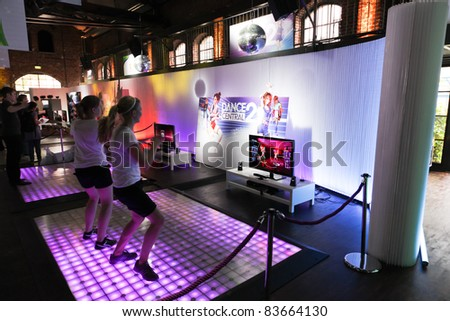 COLOGNE - AUGUST 16: Female videogamers playing with Kinect and Dance Central 2 at GamesCom 2011, the most important European video games Expo August 16, 2011 in Cologne, DE - stock photo