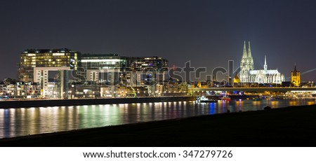 cologne city with Cathedral and crane houses at night in germany - stock photo