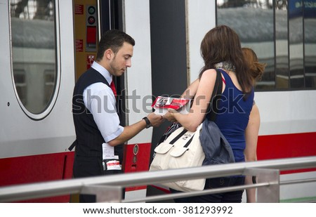 Cologne, Germany - August 30, 2013: Train conductor checks the tickets of female travelers on an international train in the railway station of Cologne, Germany on August 30, 2013 - stock photo