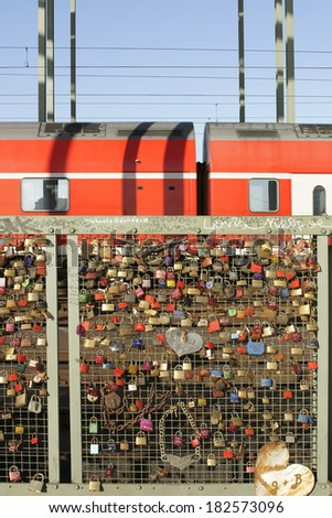 COLOGNE, GERMANY - FEBRUARY 2: Love locks and hearts at the fence of the Hohenzollern bridge with a red train on February 02, 2014 in Cologne / Hohenzollern Bridge Cologne