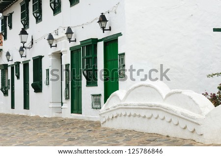 Colombia, Beautiful white villa with shingle roofs hidden behind walls in colonial Villa de Leyva. Paveed small street with the typical colonial. building - stock photo