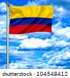 Colombia waving flag against blue sky - stock photo