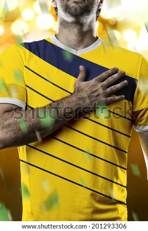 Colombian soccer player, listening to the national anthem with his hand on his chest. On a yellow lights background. - stock photo